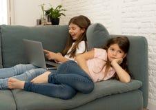 Hemfallen ung flicka f?r internet som anv?nder b?rbara datorn som ignorerar hennes ledsna ensamma mer unga syster royaltyfria bilder