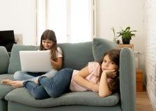 Hemfallen ung flicka f?r internet som anv?nder b?rbara datorn som ignorerar hennes ledsna ensamma mer unga syster royaltyfri fotografi