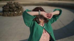 Hemfallen ung kvinna för mode som framme bär den gröna silade tyckande om solen på en springbrunn av en slott arkivfilmer