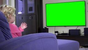 Hemfallet liten flickapunktfinger och våg som ser tv Grön chromatangentskärm arkivfilmer