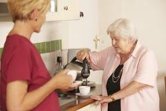 Hemhjälp som delar kopp te med den höga kvinnan i kök arkivfoto