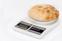 Hemhjälplägenhetbröd på en digital skala för kök Arkivbild