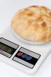 Hemhjälplägenhetbröd på en digital skala för kök Royaltyfri Fotografi