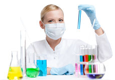 Сhemist holds a vial with blue liquid. Female chemist in respirator holds a vial with blue liquid, isolated on white Royalty Free Stock Photography