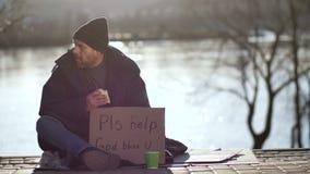 Hemlös man som äter smörgåsen och tiggerin för hjälp stock video
