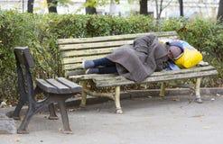 Hemlös man som sovar på en bänk arkivfoto