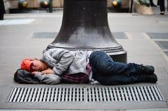 Hemlös man som sover på gatan i Paris Royaltyfri Bild