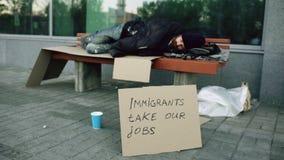 Hemlös och arbetslös europeisk man med pappteckensömn på bänk på stadsgatan på grund av invandrarekris in royaltyfri bild