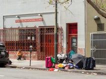 Hemlös- och droganvändare ställer upp utanför fläskkarrén som inhyser Clini royaltyfri fotografi