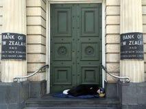 Hemlös sömn under dörröppningen av den nyazeeländska banken Arkivbild