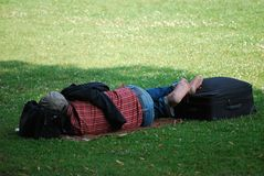 Hemlös som ligger på gräsmattan Arkivbild