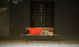 Hemlös som sover i en bänk Royaltyfri Fotografi