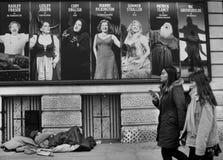 Hemlös tiggare som sover på den Leicester fyrkanten i London Royaltyfri Bild