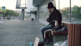 Hemlös ung man som äter smörgåsen och dricker alkohol från pappers- påse på bänk på stadsgatan i afton stock video