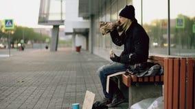 Hemlös ung man som äter smörgåsen och dricker alkohol från pappers- påse på bänk på stadsgatan i afton arkivbilder