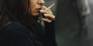 Hemlös vuxen kvinna som röker cigarettböjelse Arkivfoton
