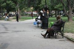 Hemlösa män och kvinnor i en stad parkerar Fotografering för Bildbyråer