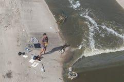 Hemlösa manwashes i floden Arkivbild