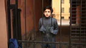 Hemlösa tonåriga blickar in i kameran till och med ett stålgaller lager videofilmer