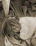 Hemlöst barn som lägger ner i en gammal ask Royaltyfria Foton