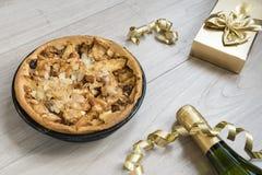 Hemlagad äppelpaj, med champagne och guld- gåva royaltyfri foto