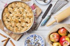 Hemlagad äppelpaj och ingredienser på en lantlig tabell Arkivfoto