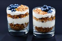 Hemlagad bakad granola med yoghurt och blåbär i ett exponeringsglas på arkivfoton