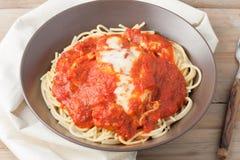 Hemlagad bröad kotlett i tomatsås och smältt ost över spagetti arkivbilder