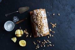 Hemlagad citronkaka med russin, muttrar och vaniljglasyr på kaka Arkivbild