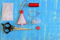 Hemlagad filtjulgran, pappers- mall, filt, tråd, visare, stift, sax på en träbakgrund med kopieringsutrymme Royaltyfri Foto