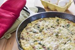 Hemlagad frittata som göras med broccoli, bacon, spenat och champinjoner royaltyfri bild