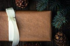 Hemlagad gåva med den granträdet och kotten som bakgrund är kan det använda julillustrationtemat Royaltyfria Foton