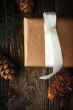 Hemlagad gåva med lodlinje för granträd och kotte som bakgrund är kan det använda julillustrationtemat Royaltyfri Bild