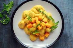 Hemlagad gnocchi för Butternutsquash med den lösa raket i en platta Arkivfoto