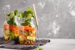 Hemlagad grön sallad i en glass krus med bakade kikärtar, guacam Arkivbild