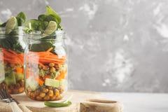Hemlagad grön sallad i en glass krus med bakade kikärtar, guacam Royaltyfri Bild