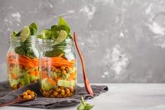 Hemlagad grön sallad i en glass krus med bakade kikärtar, guacam Arkivfoto