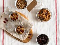 Hemlagad granola med muttrar och frukter i exponeringsglaskrus p? vit linnebakgrund Top besk?dar arkivbild