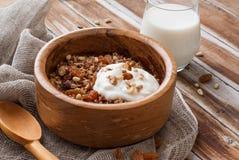 Hemlagad granola med muttrar, russin och yoghurt i en träbunke arkivfoto