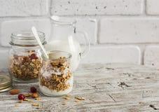 Hemlagad granola och naturlig yoghurt på en ljus träyttersida Sund mat, sund frukost Arkivfoto
