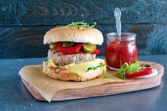 Hemlagad hamburgare med bröd, ost, tomaten, grönsallat, tomatsås, knipor och lökar på en träskärbräda med kruset av tomaten Royaltyfria Bilder