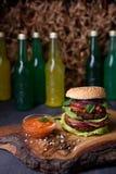 Hemlagad hamburgare på träportionbräde med lemonad, kryddig tomatsås, det salta havet och örter Arkivbild