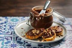 Hemlagad hasselnötkräm i bunke med hasselnötmuttrar och skivor av rostat bröd med chokladpralin på träbakgrund med kopieringsutry royaltyfri bild