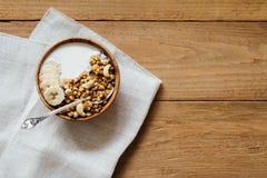 Hemlagad havremjölgranola med yoghurt i träbunke Arkivfoto
