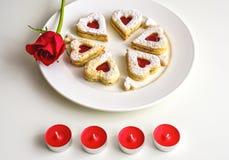 Hemlagad hjärta formade mandelLinzer kakor på den vita plattan Årsdag för ffor för röda rosor för romantisk aktivering och steari Royaltyfri Fotografi