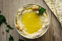 Hemlagad hummus på det lantliga köksbordet med arabiskt bröd på en sida arkivbild