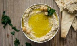 Hemlagad hummus på det lantliga köksbordet med arabiskt bröd på en sida Arkivfoto