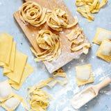 Hemlagad italiensk pasta, ravioli, fettuccine, tagliatelle på ett träbräde och på en blå bakgrund Matlagningprocessen royaltyfri bild