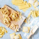 Hemlagad italiensk pasta, ravioli, fettuccine, tagliatelle på ett träbräde och på en blå bakgrund Matlagningprocessen royaltyfria foton