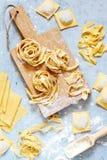 Hemlagad italiensk pasta, ravioli, fettuccine, tagliatelle på ett träbräde och på en blå bakgrund Matlagningprocessen arkivfoto